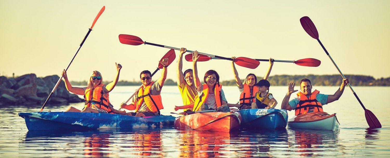 group of kayakers raising paddles