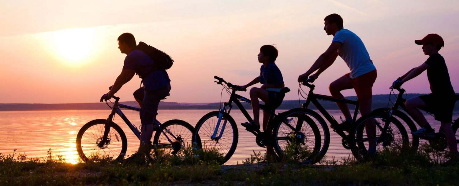 family riding their bikes at sunset
